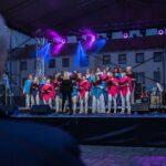 Chórzyści śpiewają w świetle kolorowych jupiterów