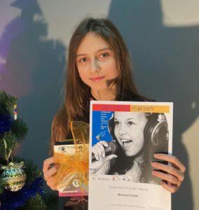 Kilkunastoletnia, ciemnowłosa dziewczynka trzyma w lewej ręce dypolm, a w prawej nagrodę. Obok stoi choinka