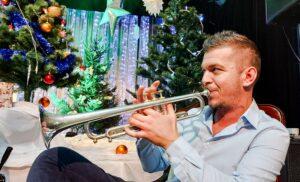 Na pierwszym planie mężczyzna grający na trąbce. W tle świąteczna dekoracja - ozdobione choinki i światełka