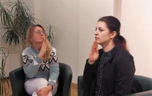 """Zdjęcie przedstawia dwie kobiety. Obie pokazują gest """"słabosłyzący"""" w polskim języku migowym"""