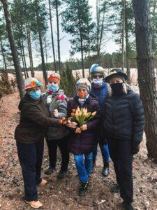 Pięć kobiet stoi wśród drzew. Kobieta w środku trzyma bukiet tulipanów. Kobiety na twarzach mają maseczki higieniczne.