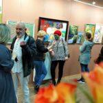 Sala wystawowa. Na ścianach kolorowe obrazy. Przy nich stoją ludzie, rozmawiają.