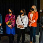 Pięć kobiet, stoją obok siebie. Mają maseczki higieniczne na twarzach. Jedna trzyma bukiet kwiatów.