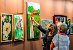 Wysawa malarstwa. Na ścianie wisza obrazy. Głównie pejzaże i kwiaty. Z prawej strony stoją dwie kobiety. Jedna dotyka płótna przedstawiaącego kobietę karmiącą kury.