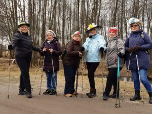 Sześć kobiet stoi obok siebie. Wspierją się na kijkach do nordic walkingu. Pora roku - wczesna wiosna. Trzy z nich mają na głowie kapelusz. W tle bezlistne drzewa.