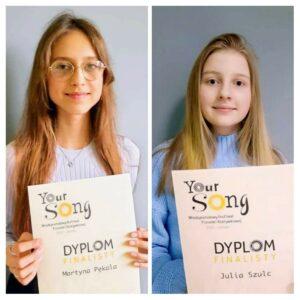 Dwie nastoletnie dziewczynki, uśmiechają sie. Każda trzyma dyplom finalistki międzynarodowego konkursu wokalnego Your Song.