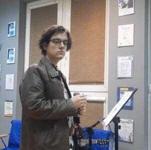 Chłopiec, nastolatek, trzyma w ręce mikrofon, przd nim stoi partytura z nutami. Chłopiec ma ciemne włosy, nosi okulary. W tle oko, na ścianie wiszą obrazki  idyplomy