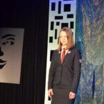 Młoda dziewczna w ciemny mundurku szkolnym, białej bluzce i czerwonym krawacie. Włsy do ramion przytrzymuje opaską.