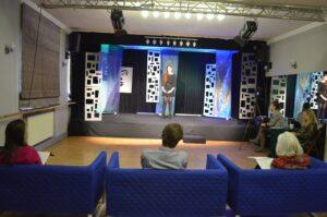 Sala widowiskowa. Na senie stoi młoda dziewczyna. Przed sceną stojąa trzy niebieskie fotele. Na każdym siedzi jedna osoba.