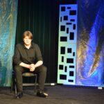Młody chłopak ubrany w ciemną koszulę i spodnie. Siedzi na krzesełku. Ręce ma oparte o kolana. Na twarzy lekki grymas.