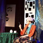 Starsza kobieta siedzi przy stoliku nakrytym zielonym obrusem. Ubrana jest w kwiecistą spódnicę, pomarańczowy żakiet. Na głowie ma beret. W rece trzyma łyżkę, której sie przygląda.