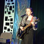 Dziweczzna gra na gitarze i śpiewa.