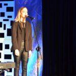 Młoda dziewczyna sstoi przy mikrofonie., Śpiewa.