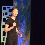 Młoda dziewczyna ubrana w ciemną bluzkę z krótkim rękawem i ciemne spodnie. Jedną rękę ma zgiętą i lekko uniesioną w górę. Coś mówi.
