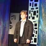 Młody chłopak stoi na scenie. Ubrany jest w ciemny garnitur i jasną koszulę. Patrzy w dal, lekko się uśmiecha.