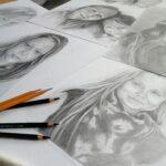 Kartki papieru, na których sa portrety narysowane ołówkiem. Na nich lezy kilka ołówków