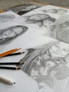 Rozłożone na podłodze kartki papieru, na których sa portrety narysowane ołówkiem. Na nich lezy kilka ołówków
