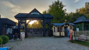 Drewniana wysoka brama wjazdowa. z daszkiem. Obok niewielki drewniany budynek w kolorze żółtym. Zachód słońca. W tle wysokie drzewa okryte listowiem.