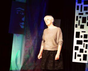 Kobieta w średnim wieku stoi na scenie. Ręce ma opuszczone wzdłuż ciała i lekko przechylona na bok głowę. Ma jasne, krótko obcięte włosy. Ubrana jest w beżową bluzkę i czarną spódnicę. Na twarzy ma lekki grymas. Coś mówi.