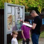Młody mężczyzna stoi przed gablotą z plakatami. Coś czyta. W ręce ma kartkę paieru. Obok niego stoi małą dziewcznka i kilkuletni chłopiec. Dzieci patrzą w odwrotnym kierunku niż mężczyzna.