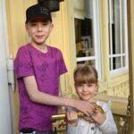 Chłopiec i dziewczynka. Trzymają w rękach duży złoty klucz. Patrzą przed siebie, uśmiechają się.