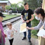 Młoda kobieta wręcza dyplom uczestnikom gry terenowej - tacie z dwójką dzieci.