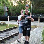 Dwóch mężczyzn. Jeden z nich niesie na barana kilkuletniego chłopca. Idą, uśmiechają się.