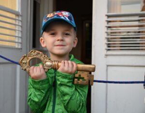 Kilkuletni chłopiec, ubrany w zielną lurtkę i czapkę z dazkiem. Uśmiecha się. Przed sobą w obu rękch trzyma duży złoty stylizowany klucz.