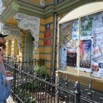 Dzieczyna i chłopak stoją przed gablotą, w której znajdują się kolorowe plakaty z informacją o wydarzeniach. Wpatrują się w nie. Chłopak ma na głowie czapkę z daszkiem. Świeci słońce.