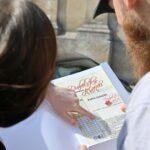 Dziewczyna i chłopak odwrócni tyłem. Przed sobą mają kartkę papieru i znformacjami. Czytają.