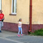 Kobieta, mężczyzna i dwoje kilkuletnich dzieci idą wzdłuż ściany parterowego budynku. Rozglądają się, jakby czegoś szukali.