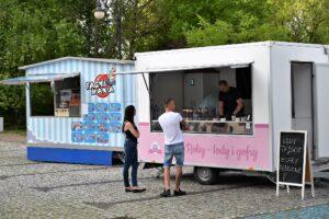 Dwa food trucki ze słodkimi przekąskami. Przed jednym stoi dwoje ludzi - kobieta i mężczyzna. Rozmawiają ze sprzedawcą.