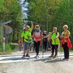 Cztery kobiety stoją na środku drogi. Wspierają sie na kijkach do nordic walkingu. Uśmiechają się. Jest słoneczna pogoda