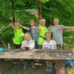 Sześć kobiet w średnim wieku. Dwie siedzą przy drewnianym stole. Pozostałe stoją im za plecami. Kobiety uśmiechają i pozują do zdjęcia.