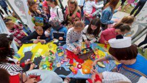 Grupa osób, zwłaszcza dzieci przy stoisku plastycznym.