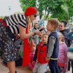 Kobieta przebrana w stój piratki nachyla się nad małym chłopcem. Trzyma w ręce mikrofon, do którego chłopiec coś mówi. W tle grupa innych dzieci.