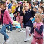 Grupa dzieci tańczyprzed sceną.