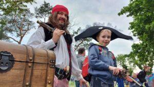 Mężczyzna przebrany w strój pirata. Na głowie ma czerwoną bandanę. W prawej ręce trzyma pistolet, opiera go na ramieniu. Obok stoi chłopiec w pirackiej czapce. Obaj patrzą przed siebie, uśmiechają się.