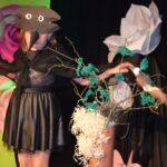 Dziewczynka w kostiumie ptaka. Obok niej stoi sztuczne drzewo.