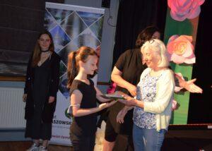Dziewczynka odbiera nagrodę w konkursie. Przed nią stoją członkowie jury.
