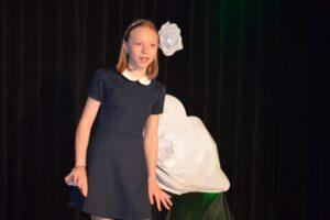 Dziewczynka ubrana w granatową sukienkę z białym kołnierzykiem. Na jasnych włosach ma przepaskę. Lekko pochyla się w bok, coś mówi