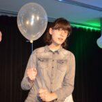Nastoletnia dziewczynka. Nosi okulary. W ręće tzyma balonik. Coś mówi.