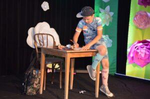 Chłopiec ubrany w koszulkę z rótkim rękawem i krótkie spodenki. Na głowie ma czapkę z daszkiem. Siedzi naa skraju stołu. Coś pisze na rozłożonej na nim kartce.