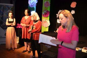 Cztery kobiety. Ta na pierwszym planie ma jasne włosy, ubrana jest w różowa sukienkę. Wpatruje się w kartki papieru, które trzyma w dłoniach. Pozostałe trzy kobiety w głębi uśmiechaają się.