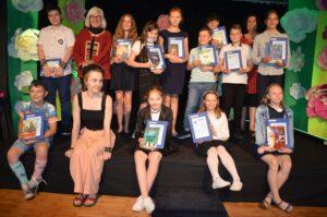 Grupa laureató iuczestników konkursu na scenie. W rękach trzymają książki i dyplomy
