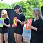 Trzy aktorki ubrane czarne stroje. Trzymają w rękach kolorowe tabliczki z pojedynczymi literami: M, C, K.
