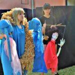 Młoda dziewczyna o jasnych włosach ubrana w niebieski strój, trzyma lalki teatralne imitujące słonie. Obok młodsza dziewczna o ciemnych włosach, nosi okulary. W rękach ma marionetkę.