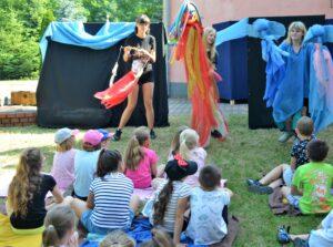 Scena plenerowa. Przed czarnymi ściankami stoją trzy aktorki z lalkami teatralnymi. Przed nimi na piknikowych kocach siedzisiedzi grupa dzieci