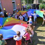 Dzieci bawiące się chustami animacyjnymi i małymi kolorowycmi piłkami.
