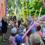 Grupa dzieci z kolorowymi podłużnymi balonami. Stoją twarzą w stronę instruktorki, która coś do nich mówi. Kobieta ma jasne włosy i czarną sukienkę.